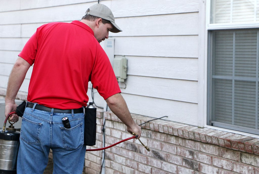 Pest control technician treating outside of home with spray