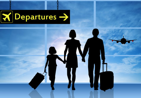 Family in airport under Departures sign