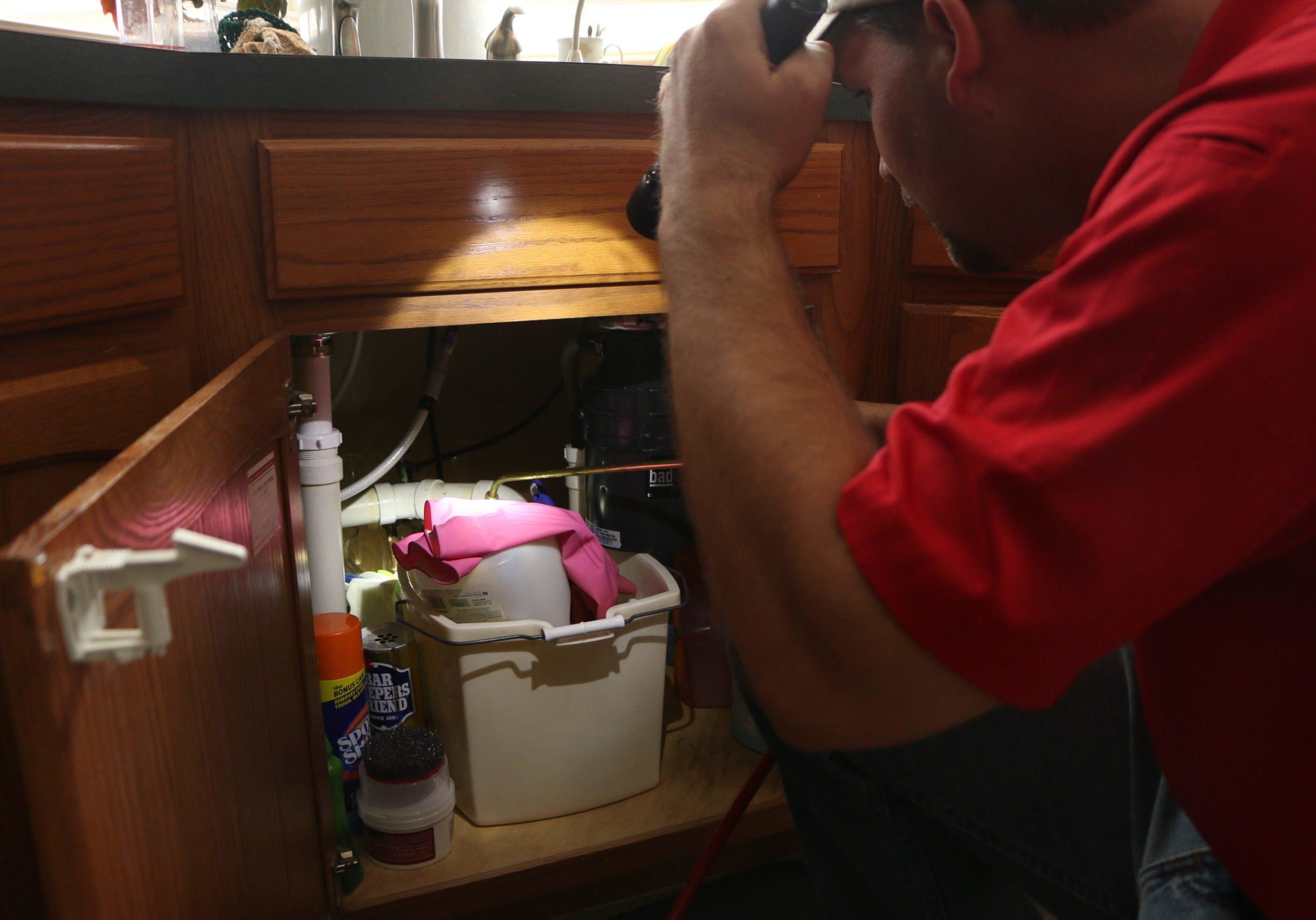 Pest control technician shining flashlight under kitchen sink