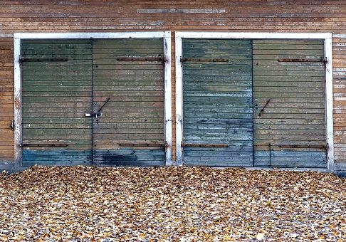 Garage doors made of knotted wood in autumn