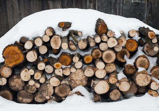 the stack of the snowy firewood on old wooden background.